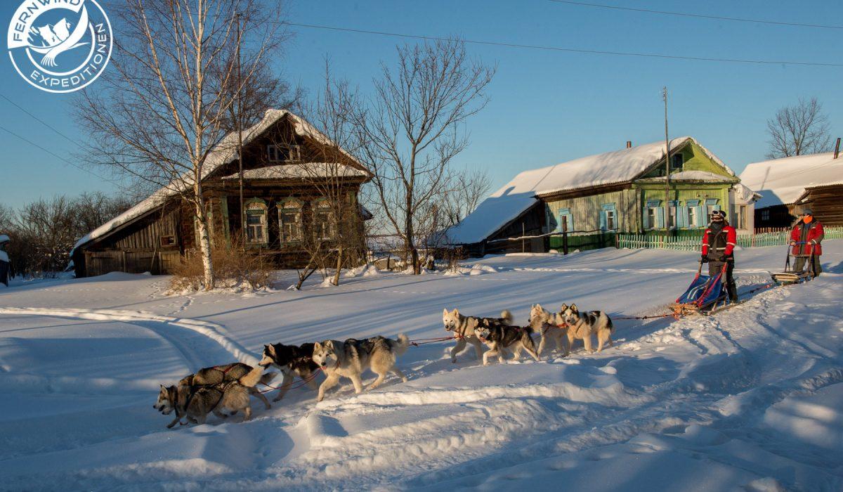 vorbei an traditionellen Häusern