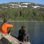 Zwei Menschen sitzen auf einem Felsen und schauen aufs Wasser