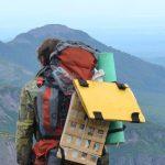 Ein Mensch mit Rucksack steht vor den Bergen Kamtschatkas