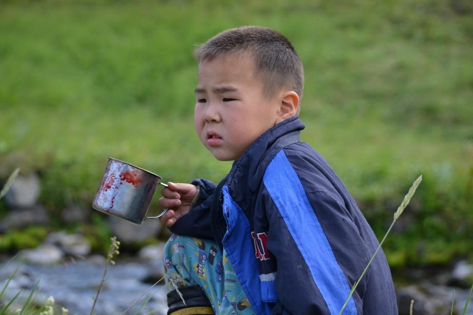 Ewenen-Junge mit Tasse an einem Bach
