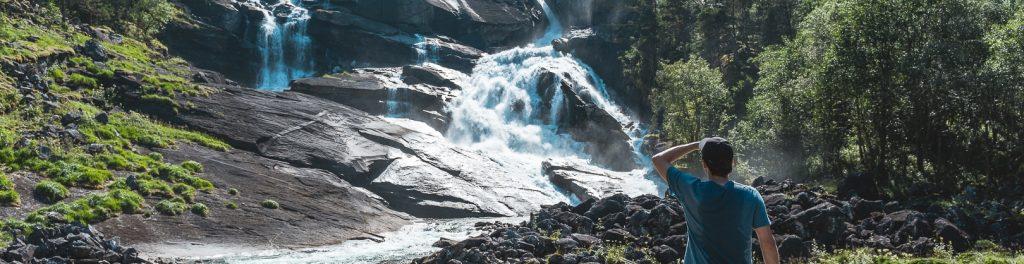trekking Tour Norwegen Mensch steht vor Wasserfall
